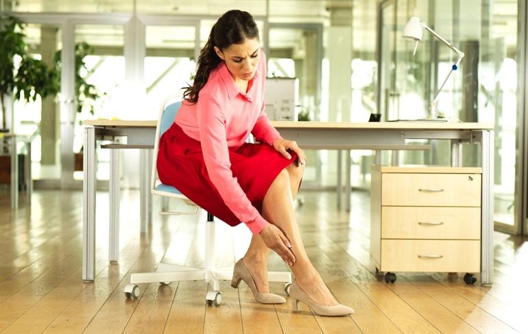 Žena sjedi na stolici u kancelariji i dodiruje nogu