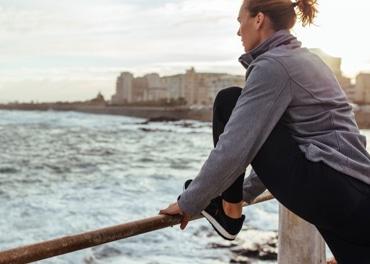 Žena se naginje prema naprijed, isteže noge nakon trčanja po gradu  kako bi spriječila vensku insuficijenciju