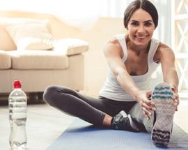 Žena radi vježbe za vene na prostirci za jogu da spriječi osjećaj otežanih nogu