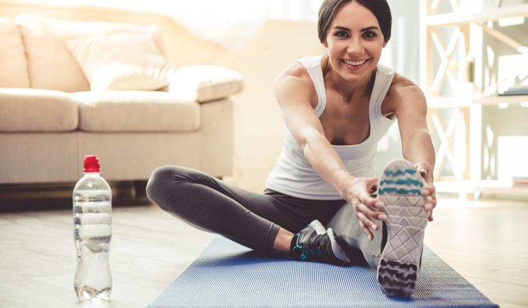 Žena se naginje naprijed da istegne obje noge na prostirci za jogu kako bi spriječila vensku insuficijenciju.