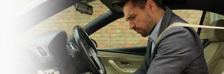 Muškarac sjedi u autu, s teškim nogama